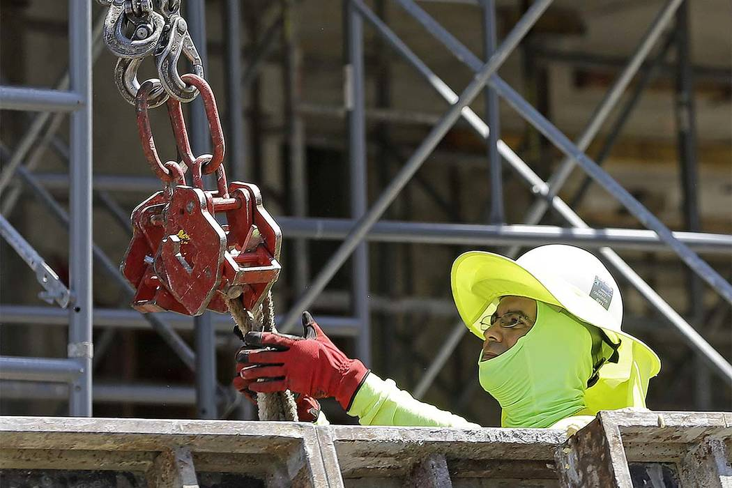 In this Thursday, June 15, 2017, photo, a construction worker continues work on a condominium project in Coral Gables, Fla. On Friday, July 7, 2017, the Labor Department will release the U.S. jobs ...