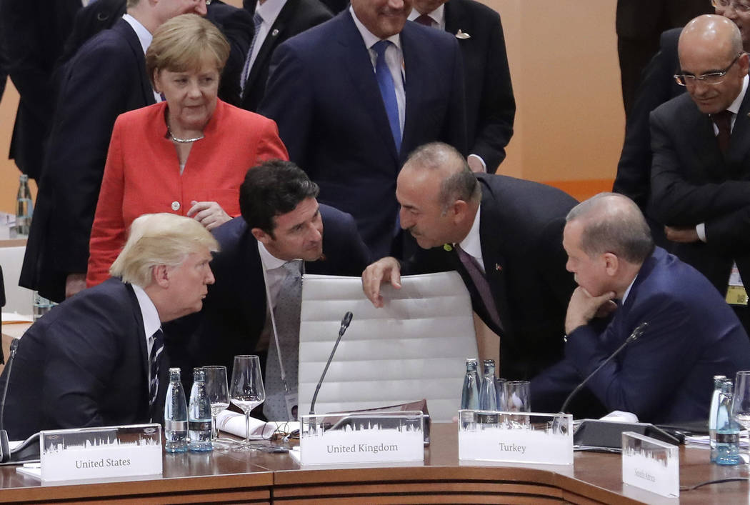 German Chancellor Angela Merkel looks on as President Donald Trump, left, talks to Turkey's Foreign Minister Mevlut Cavusoglu and Turkish President Recep Tayyip Erdogan, right, prior to the first  ...