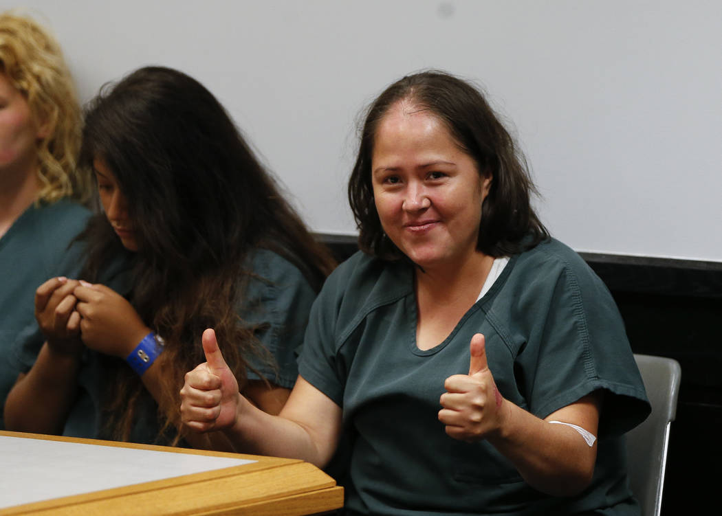 Isabel Martinez gestures towards news cameras during her first court appearance Friday, July 7, 2017, in Lawrenceville , Ga. Martinez is charged with killing four of her children and their father. ...