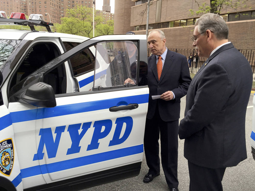 In this May 10, 2016 photo provided by the New York City Police Department, NYPD Commissioner William Bratton, second from right, examines a bullet resistant safety shield affixed to the side wind ...