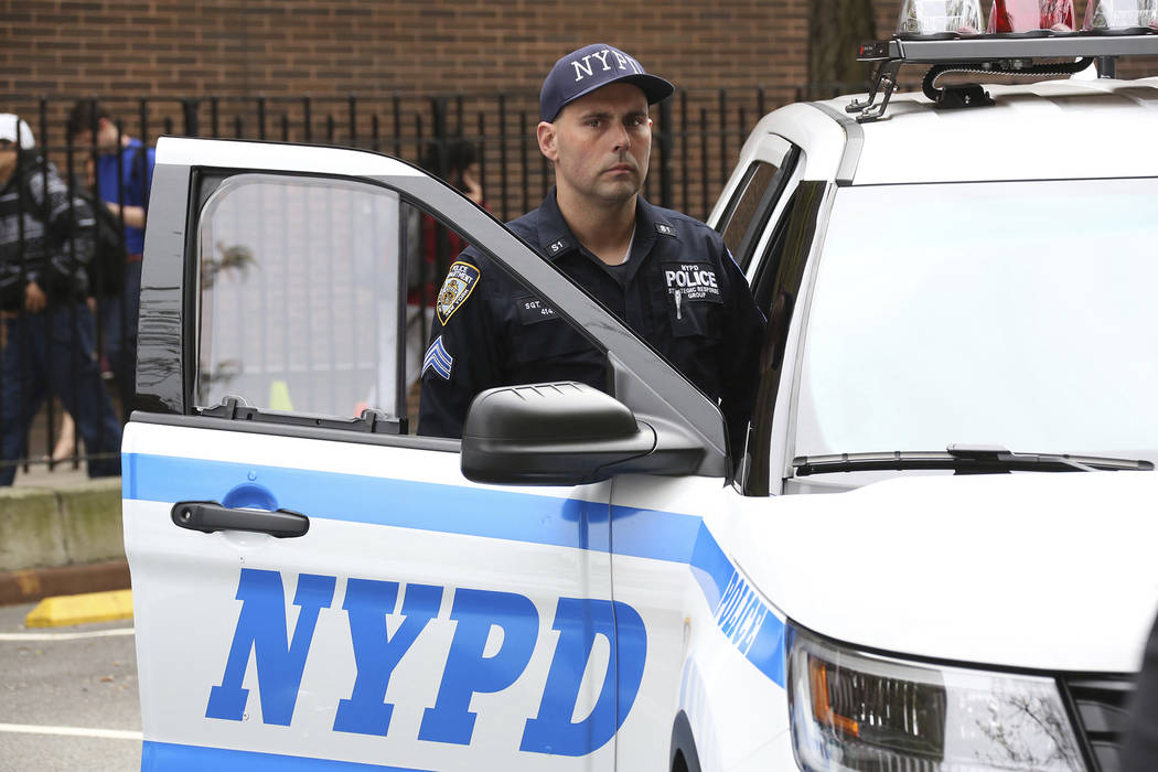 In this March 10, 2016, photo provided by the New York City Police Department, an NYPD sergeant opens the door of a patrol car with a bullet resistant glass shield fitted over the passenger side w ...