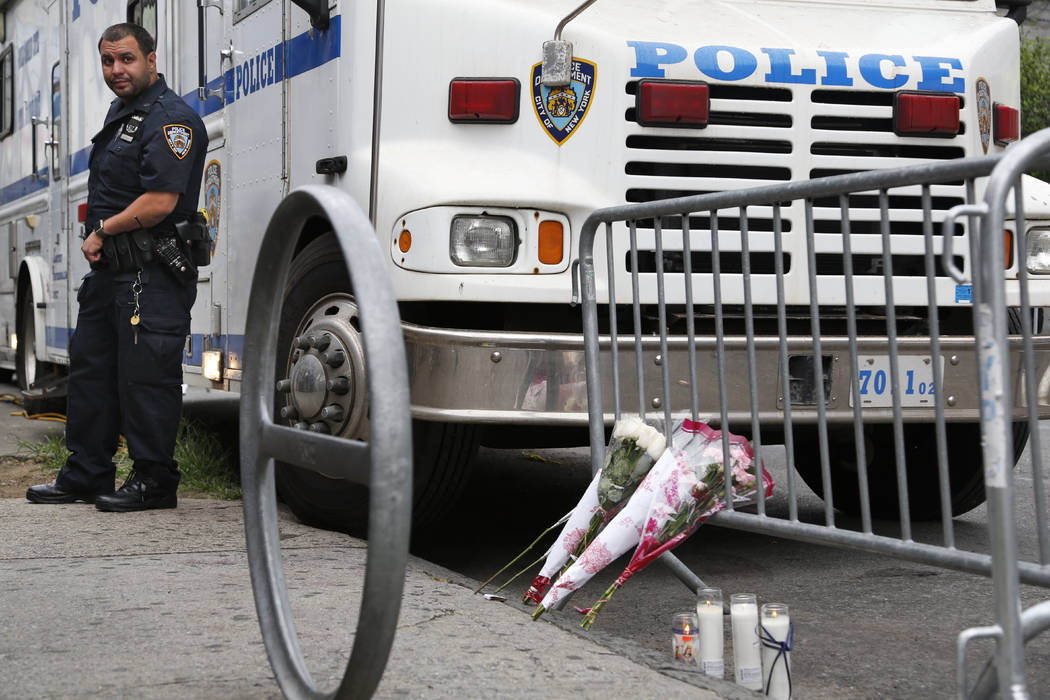 A police officer stands near the site where an officer was killed, and flowers have been left, in the Bronx section of New York, Thursday, July 6, 2017. Police officer Miosotis Familia was shot to ...