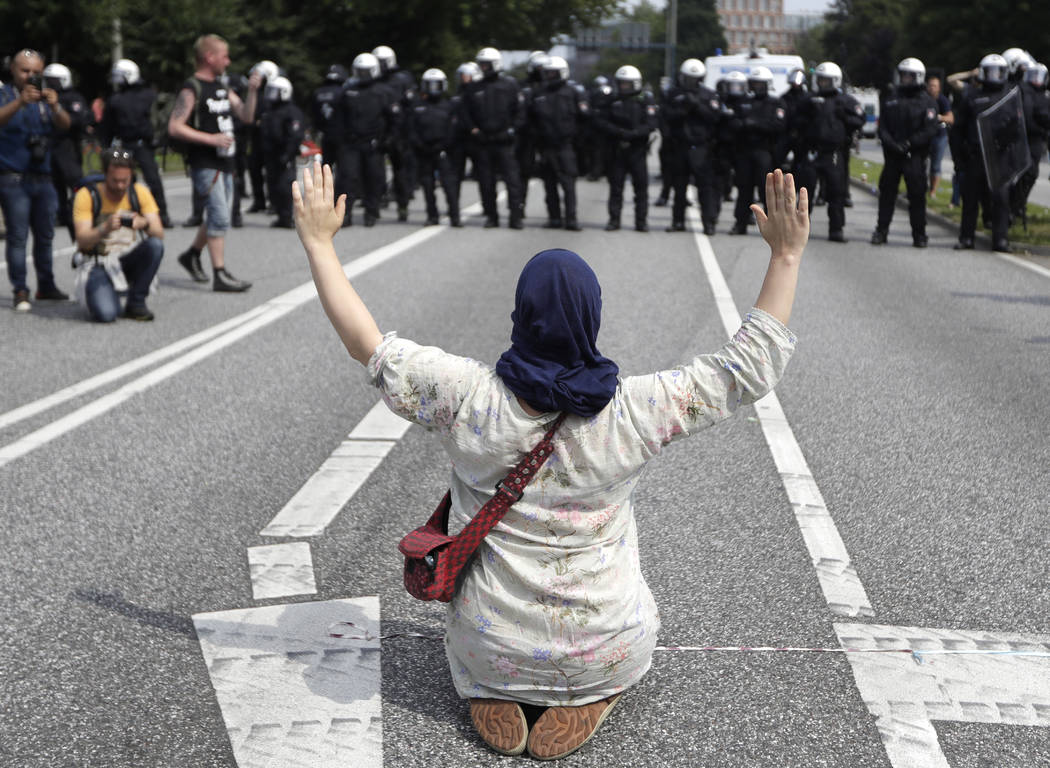 A woman raises her arms as she kneels on a road in front of police officers on the first day of the G-20 summit in Hamburg, northern Germany, Friday, July 7, 2017. The leaders of the group of 20 m ...