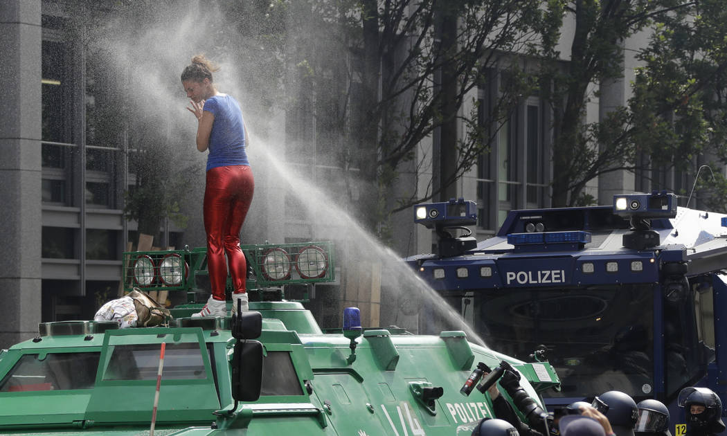 A woman is pepper-sprayed by police after she climbed an armored police vehicle on the first day of the G-20 summit in Hamburg, northern Germany, Friday, July 7, 2017. The leaders of the group of  ...