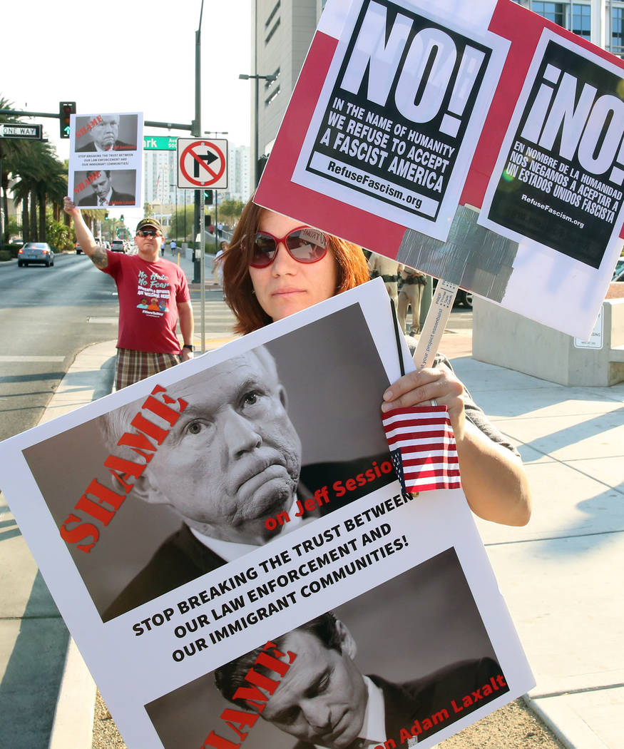 A protester, who declined to give her name, protests against sanctuary cities ban outside a federal building where Attorney General Jeff Sessions delivers a speech to federal, state and local law  ...