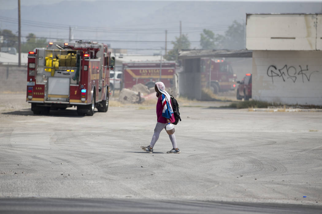 A person walks at the closed Moulin Rouge Hotel as fire crews work on a fire on the property in Las Vegas, Friday, July 7, 2017. Erik Verduzco/Las Vegas Review-Journal