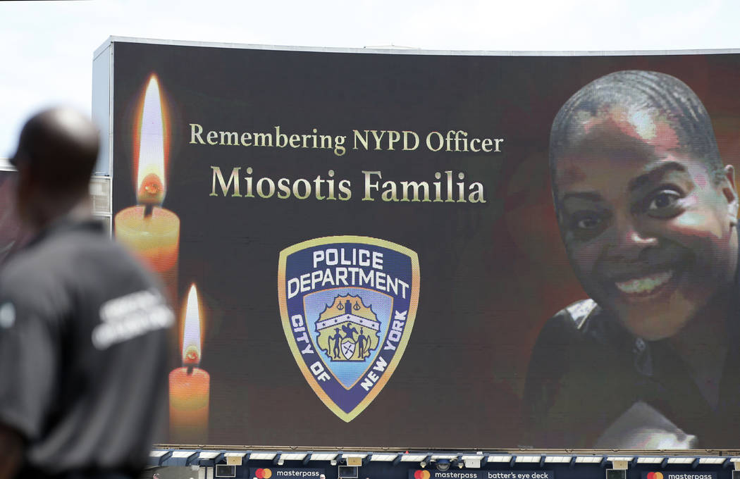 A security guard stands at attention as New York Police Department officer Miosotis Familia is memorialized before the start of a baseball game between the New York Yankees and the Toronto Blue Ja ...