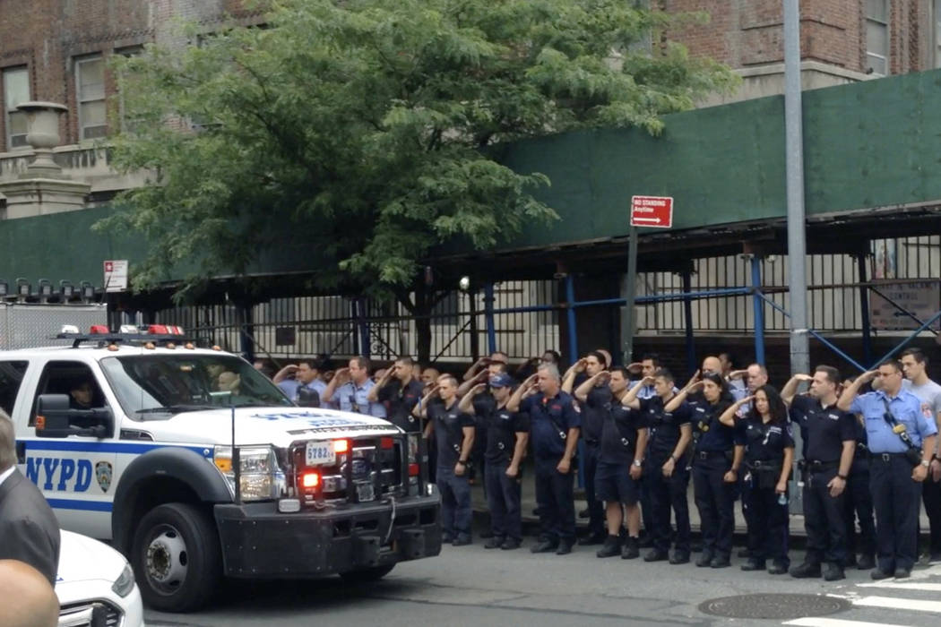 In this image taken from video, New York City Police and firefighters salute as the motorcade with the body of fallen NYPD officer Miosotis Familia leaves Bellevue Hospital in New York enroute to  ...