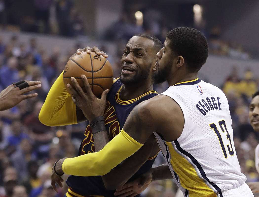 Cleveland Cavaliers' LeBron James, left, goes to the basket against Indiana Pacers' Paul George during the first half in Game 4 of a first-round NBA basketball playoff series, Sunday, April 23, 20 ...
