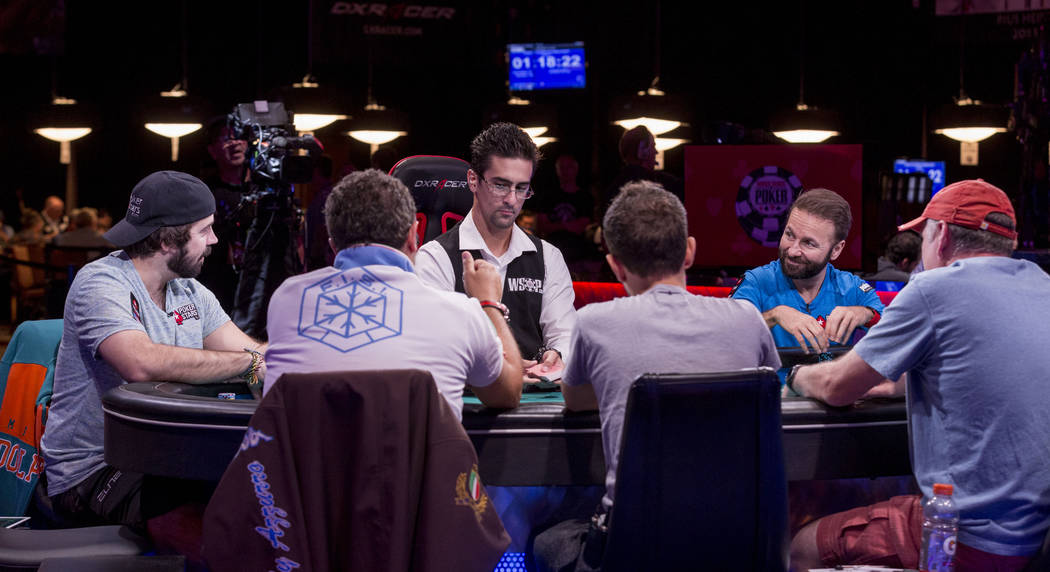 Jason Mercier, left, looks at opponent  Daniel Negreanu across the table during the World Series of Poker $10,000 no-limit hold 'em Main Event at the Rio Convention Center in Las Vegas, Monday, Ju ...