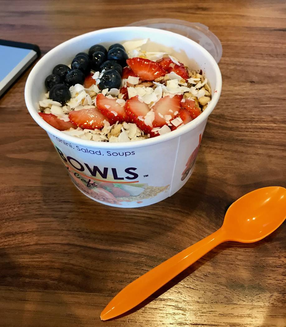 """Many customers order to go, as well. Pictured: The July """"Liberty Bowl"""" special: A frozen and blended açaí base with almond milk, strawberries, banana and raspberries topped with hemp and flax se ..."""