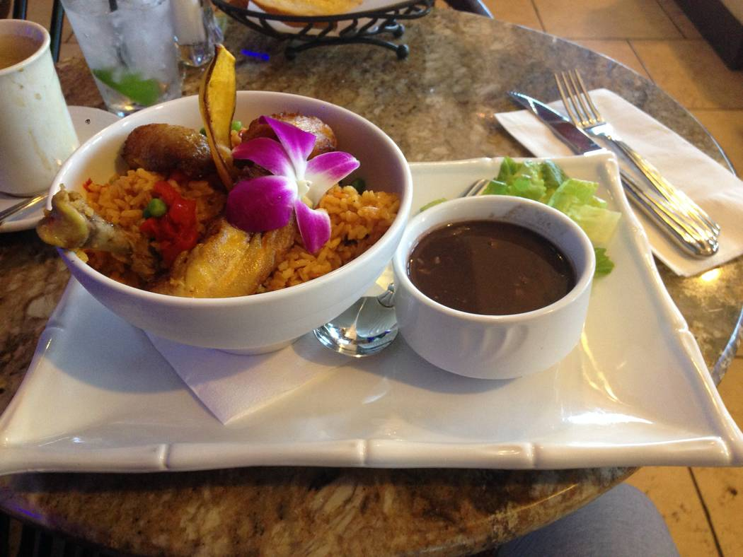 The arroz con pollo a la chorrera (chicken with valencia rice, bell peppers, roasted red peppers and fried sweet plantains) with black beans at the Florida Cafe Cuban Bar and Grill on July 4, 2017 ...