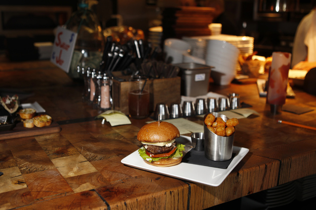 A butter burger is seen served with boursin cheese, cheddar, lettuce, and tomato with a side of tater tots during dinner service at Carson Kitchen restaurant, 124 S. Sixth St. in Las Vegas, on Sat ...