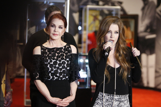 "Priscilla Presley, left, listens to her daughter Lisa Marie Presley speak during a media day for the ""Graceland Presents Elvis: The Exhibition - The Show - The Experience"" at the ..."