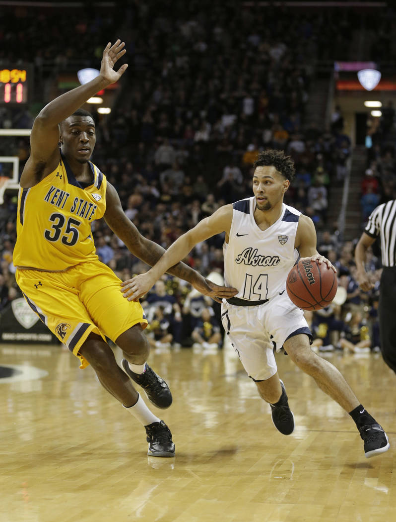 Akron's Noah Robotham, right, drives past Kent State's Jimmy Hall during the first half of an NCAA college basketball championship game of the Mid-American Conference tournament, Saturday, March 1 ...