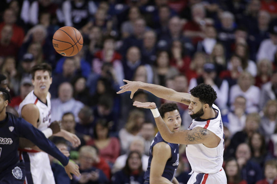 Gonzaga guard Josh Perkins, right, passes the ball in front of Akron guard Noah Robotham during the second half of an NCAA college basketball game against Akron in Spokane, Wash., Saturday, Dec. 1 ...