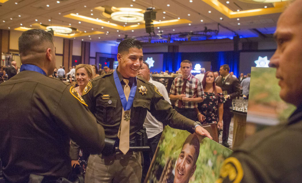 Officer Alfred Garcia, center, holds his photos after receiving a Medal of Honor during the Metropolitan Police Department's Best of the Badge gala at the Red Rock Resort in Las Vegas, Friday, Jul ...