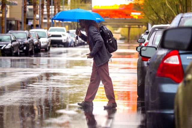 A man walks during a rain storm at Downtown Summerlin on Friday, Jan. 13, 2017. (Jeff Scheid/Las Vegas Review-Journal) @jeffscheid