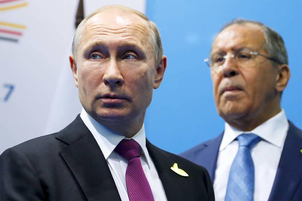 Russian President Vladimir Putin, left, and Foreign Minister Sergey Lavrov stand while waiting for Turkish President Recep Tayyip Erdogan prior to their talks at the G-20 summit in Hamburg, northe ...