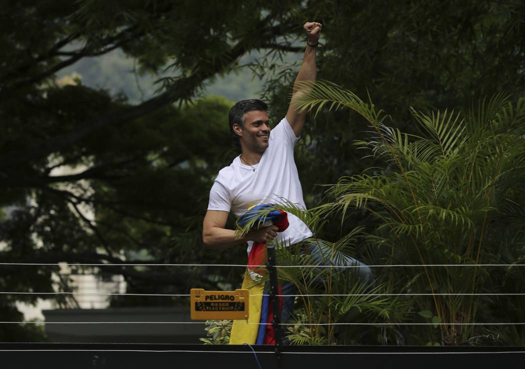 Opposition leader Leopoldo Lopez kisses a Venezuelan national flag as he greets supporters outside his home in Caracas, Venezuela, Saturday, July 8, 2017. Lopez was released from prison and placed ...