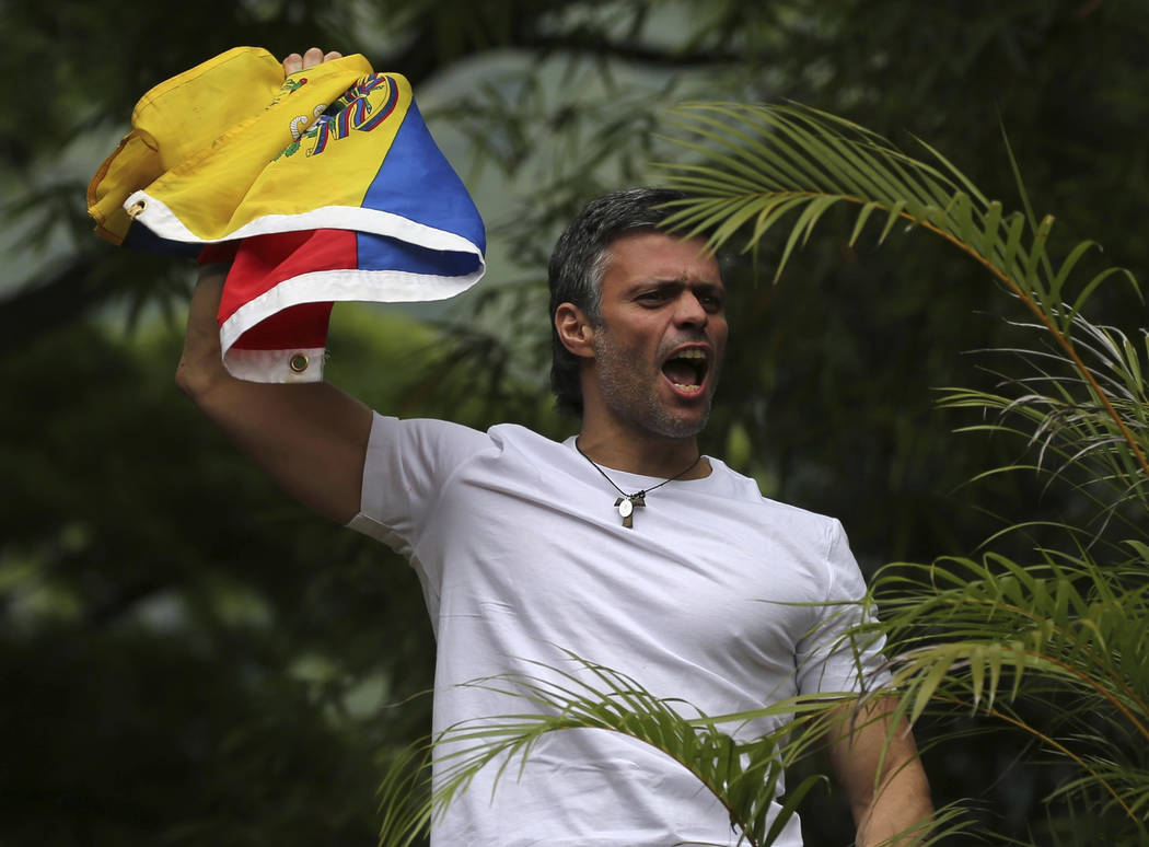 Opposition leader Leopoldo Lopez holds a Venezuelan national flag as he greets supporters outside his home in Caracas, Venezuela, Saturday, July 8, 2017. Lopez was released from prison and placed  ...