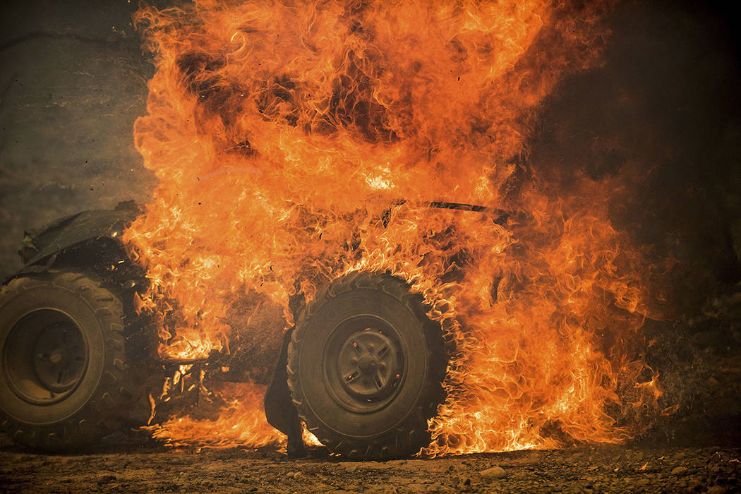 Flames from a wildfire consume an all-terrain vehicle near Oroville, Calif., on Saturday, July 8, 2017. (AP Photo/Noah Berger)