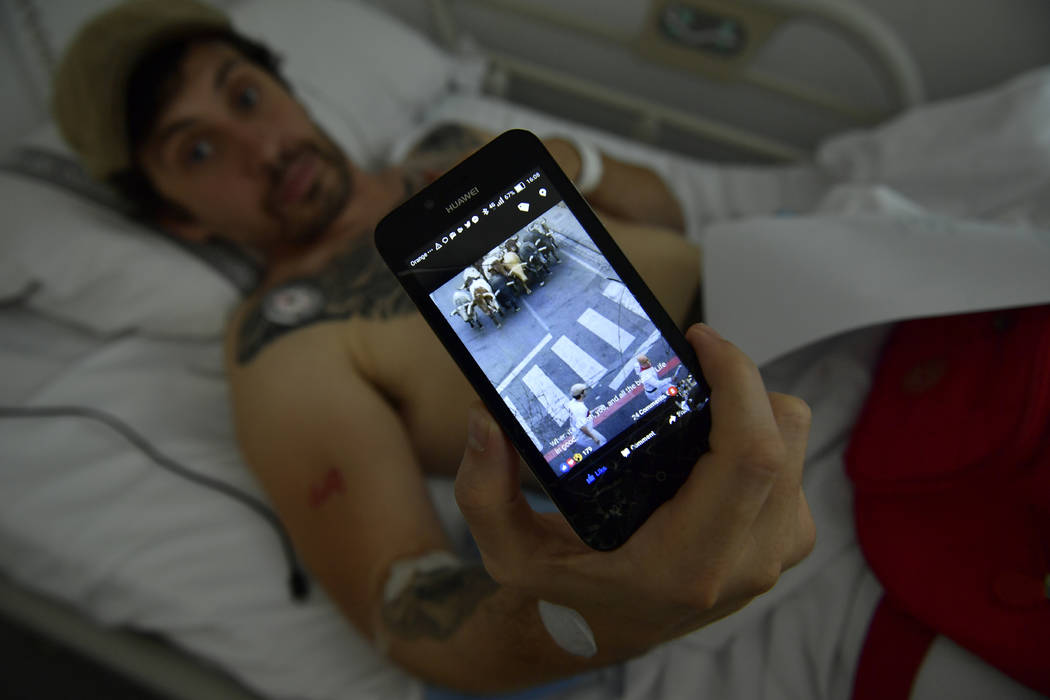 Bill Hillmann, a 35-year-old American from Chicago lying in a hospital bed, shows a photo of himself that someone sent to him during a bull run a day before he was gored at the San Fermin bull run ...