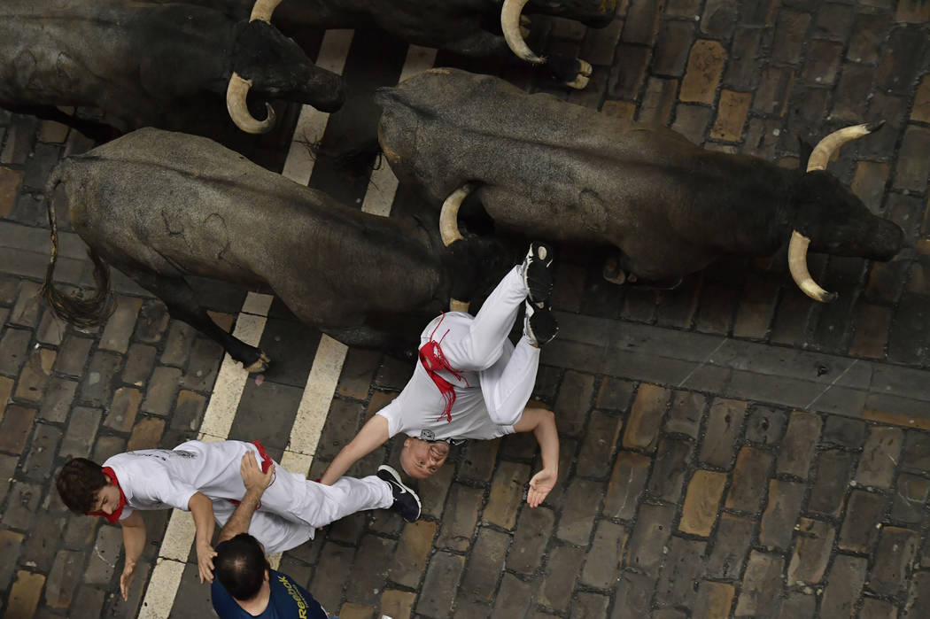 A revellers falls in front of Jose Escolar fighting bulls during the second running of the bulls at the San Fermin Festival, in Pamplona, northern Spain, Saturday, July 8, 2017. Revelers from arou ...