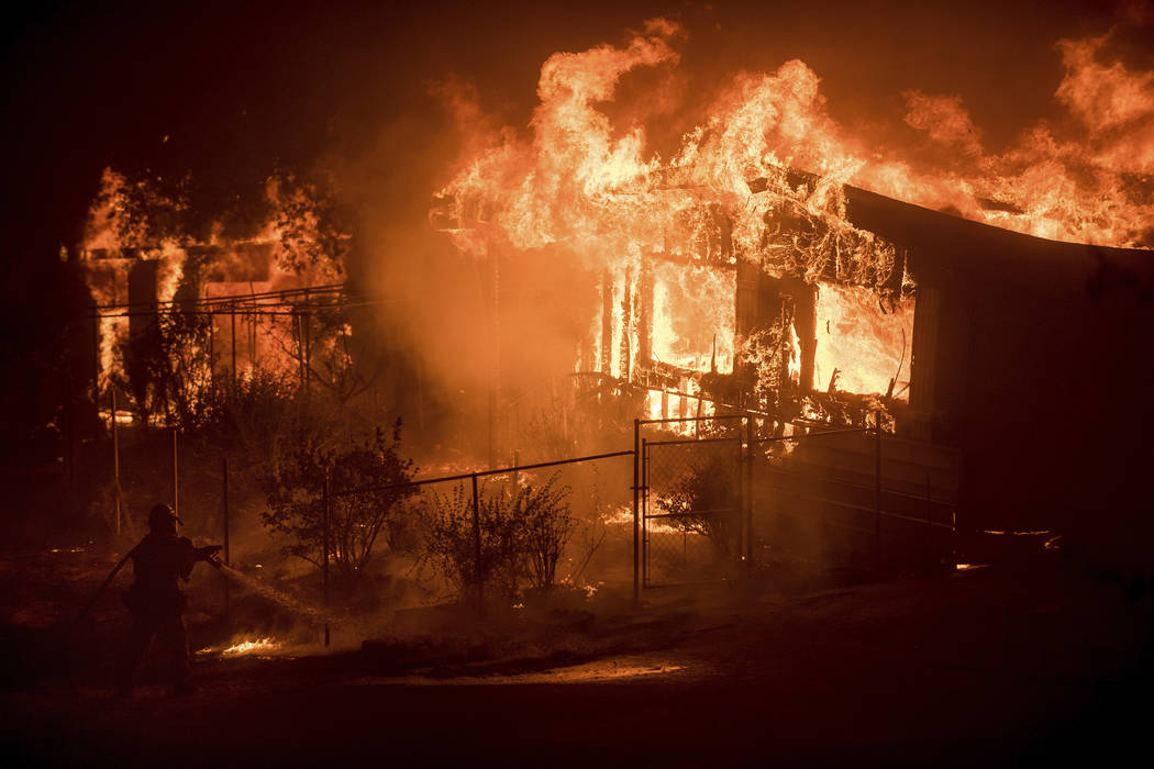 A firefighter sprays water as flames from a wildfire consume a residence near Oroville, Calif., on Sunday, July 9, 2017. (Noah Berger/AP)