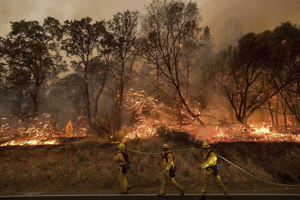 Firefighters battle a wildfire as it threatens to jump a street near Oroville, Calif., on Saturday, July 8, 2017. (Noah Berger/AP)