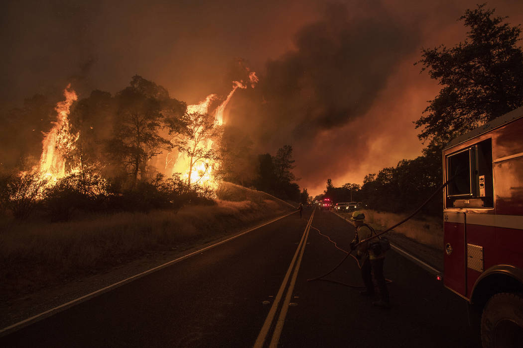 A firefighter battles a wildfire as it threatens to jump a street near Oroville, Calif., on Saturday, July 8, 2017. (Noah Berger/AP)