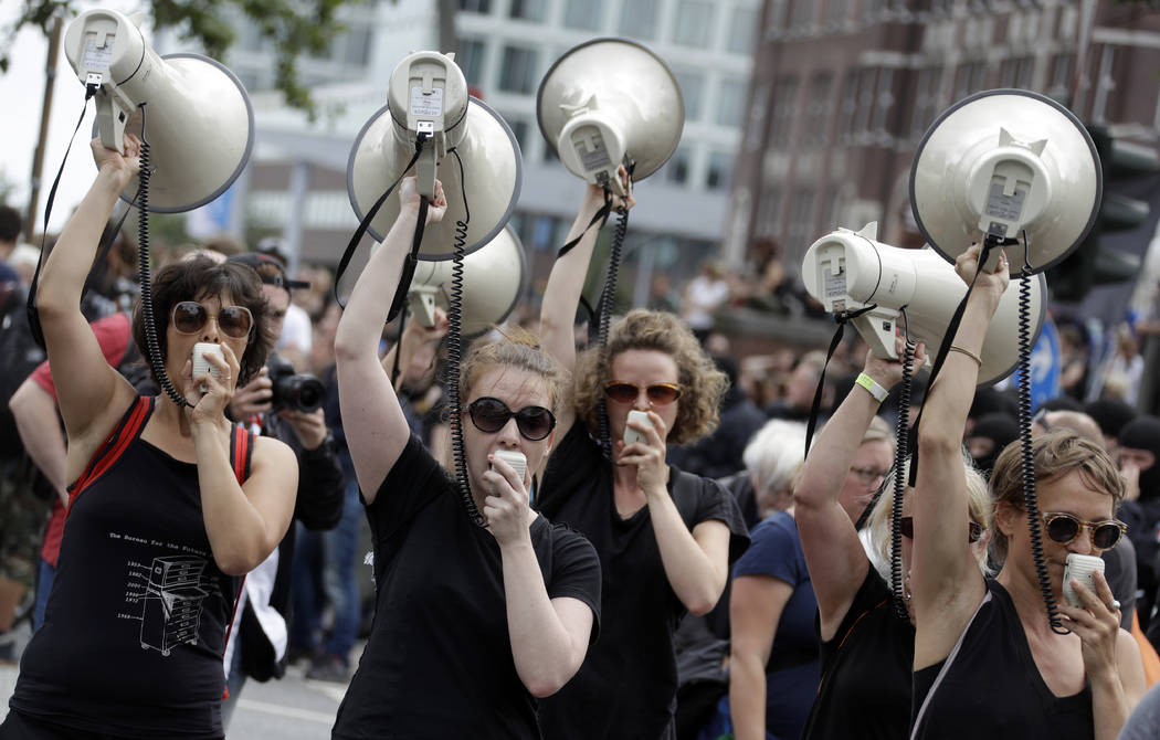 Women hold up megaphones during a protest against the G-20 summit in Hamburg, northern Germany, Saturday, July 8, 2017. The leaders of the group of 20 meet July 7 and 8. (Matthias Schrader/AP)