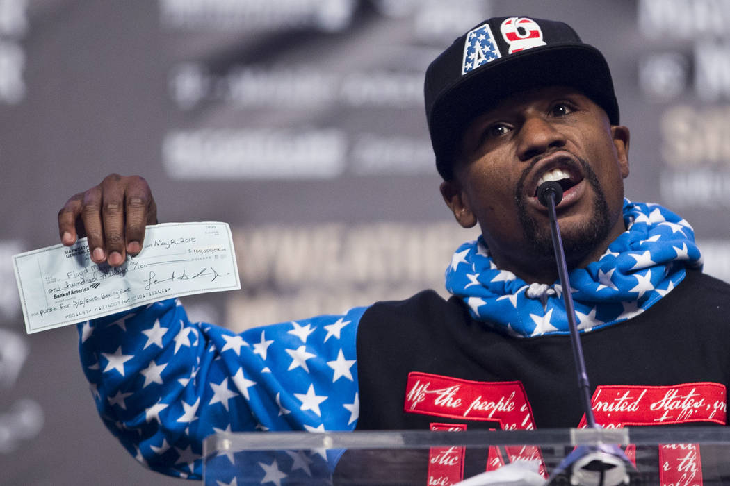 Boxer Floyd Mayweather Jr., shows his 2015 check from his fight against Manny Pacquiao during a world tour event to promote his upcoming fight against UFC fighter Conor McGregor, at Staples Center ...