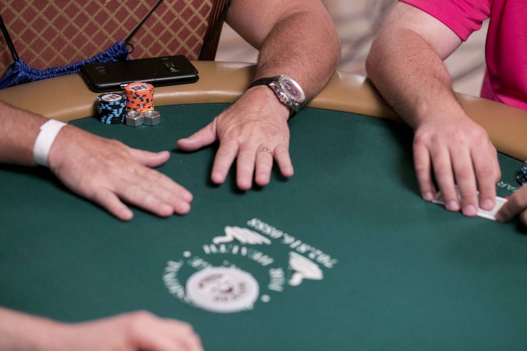 Bob Beck, left, of Santa Rosa Beach, Florida, places Hex Bolts next to his poker chips during the World Series of Poker at the Rio Convention Center in Las Vegas, Tuesday, July 11, 2017. Gabriella ...