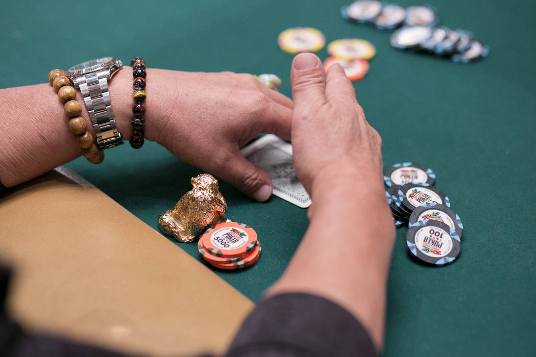 A player checks his cards near his gold Buddha statue during the World Series of Poker at the Rio Convention Center in Las Vegas, Tuesday,July 11, 2017.  Gabriella Angotti-Jones Las Vegas Review-J ...