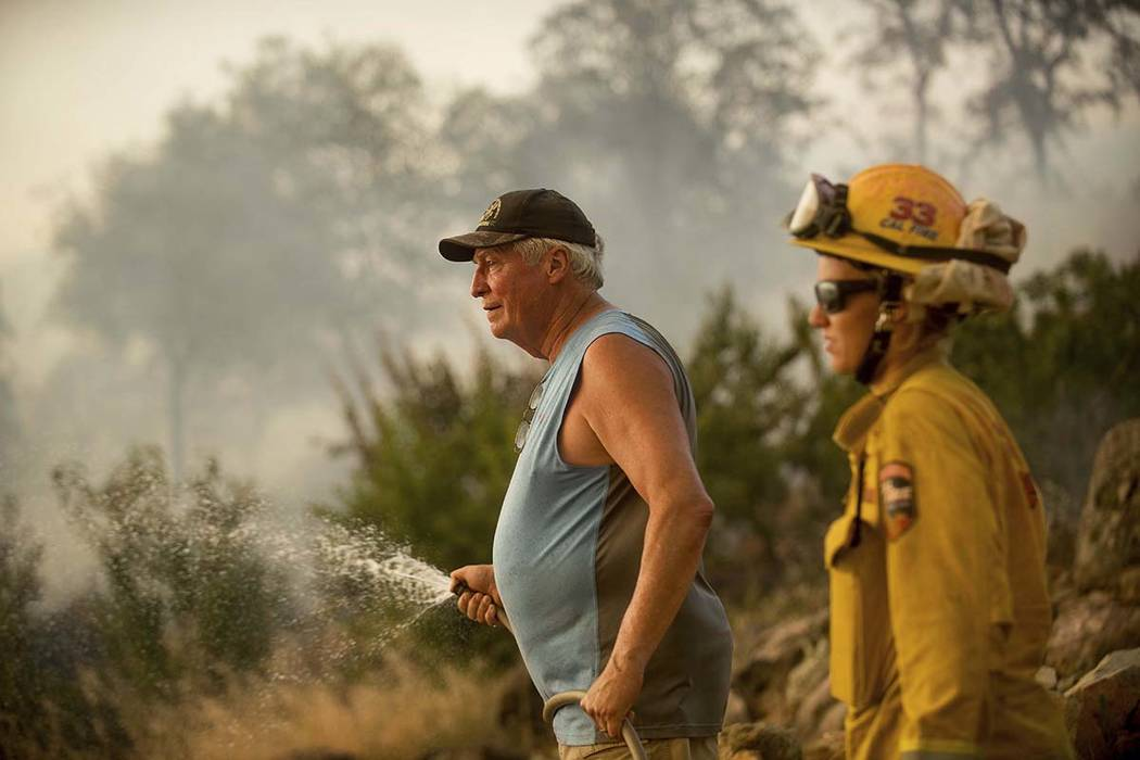Jim Berglund sprays water while defending his home as a wildfire approaches on Saturday, July 8, 2017, near Oroville, Calif.  Although flames leveled Berglund's barn, his home remained unscathed a ...