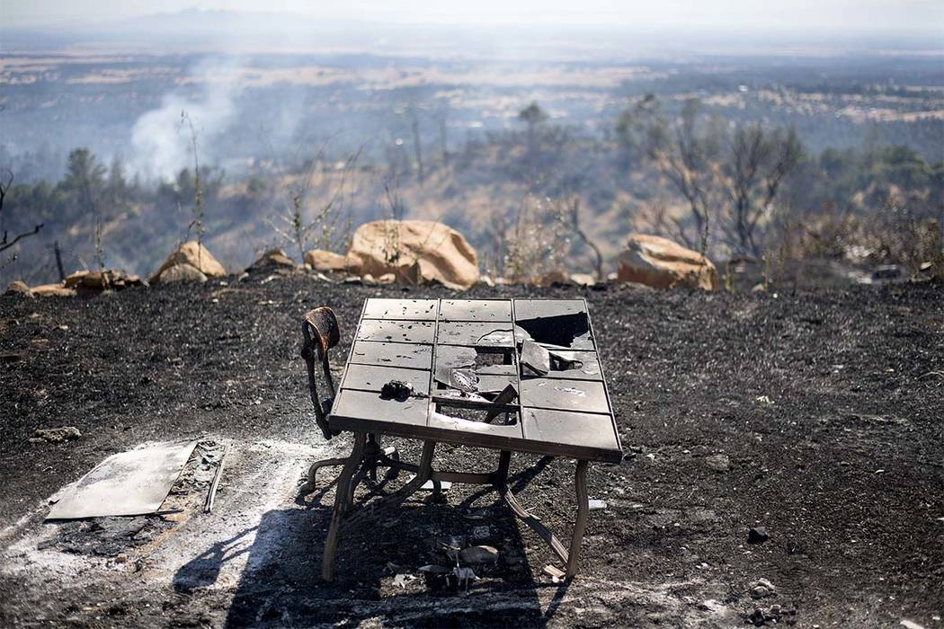 A charred desk rests outside a residence after a wildfire burned through the property on Saturday, July 8, 2017, near Oroville, Calif. The fast-moving wildfire in the Sierra Nevada foothills destr ...