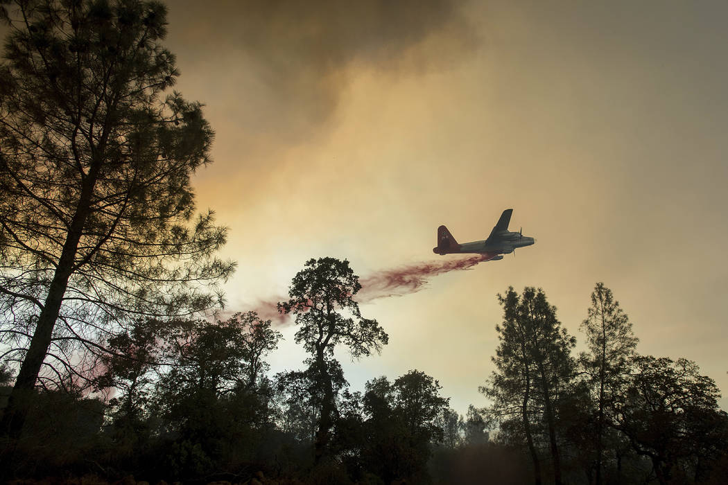 A plane drops retardant while battling a wildfire near Oroville, Calif., on Saturday, July 8, 2017. The fire south of Oroville was one of more than a dozen burning in the state as firefighters wor ...