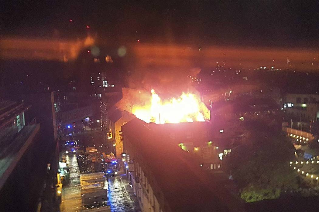 Dozens of firefighters poured water onto a fire early Monday at Camden Lock Market, which is a popular tourist destination in north London. (Mike Buckell)/AP