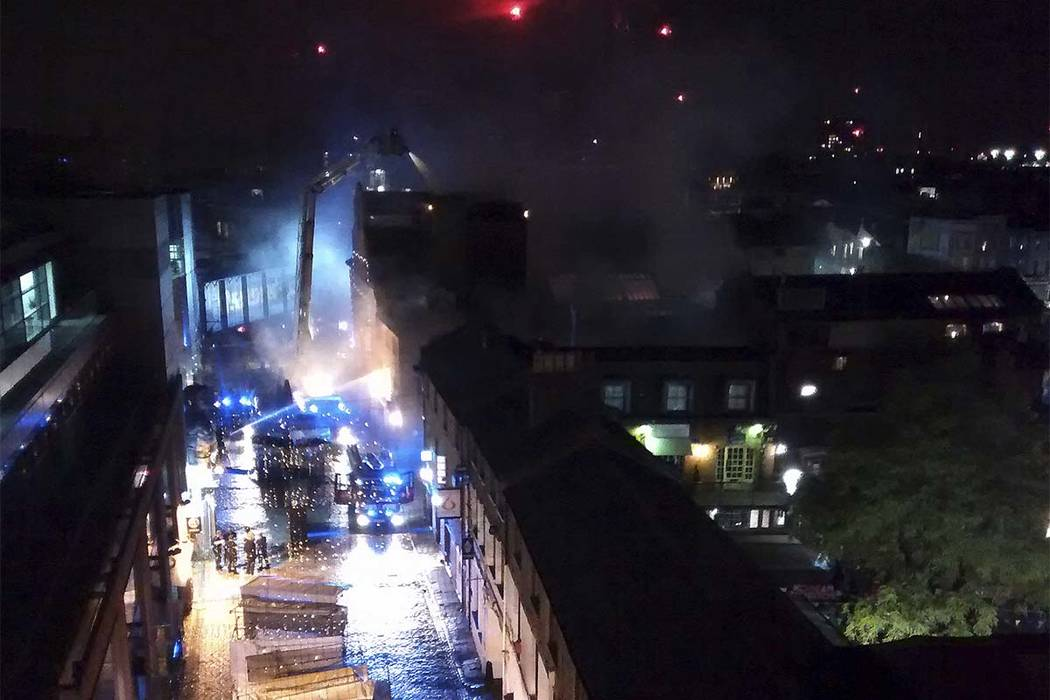 Dozens of firefighters poured water onto a big fire early Monday at Camden Lock Market, which is a popular tourist destination in north London. (Yusof Abdul-Rahman/AP)