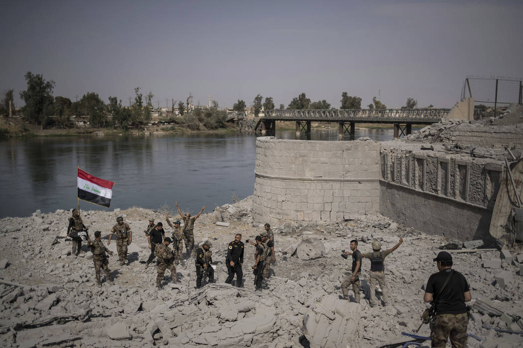 Iraqi Special Forces soldiers celebrate after reaching the bank of the Tigris river as their fight against Islamic State militants continues in parts of the Old City of Mosul, Iraq, Sunday, July 9 ...