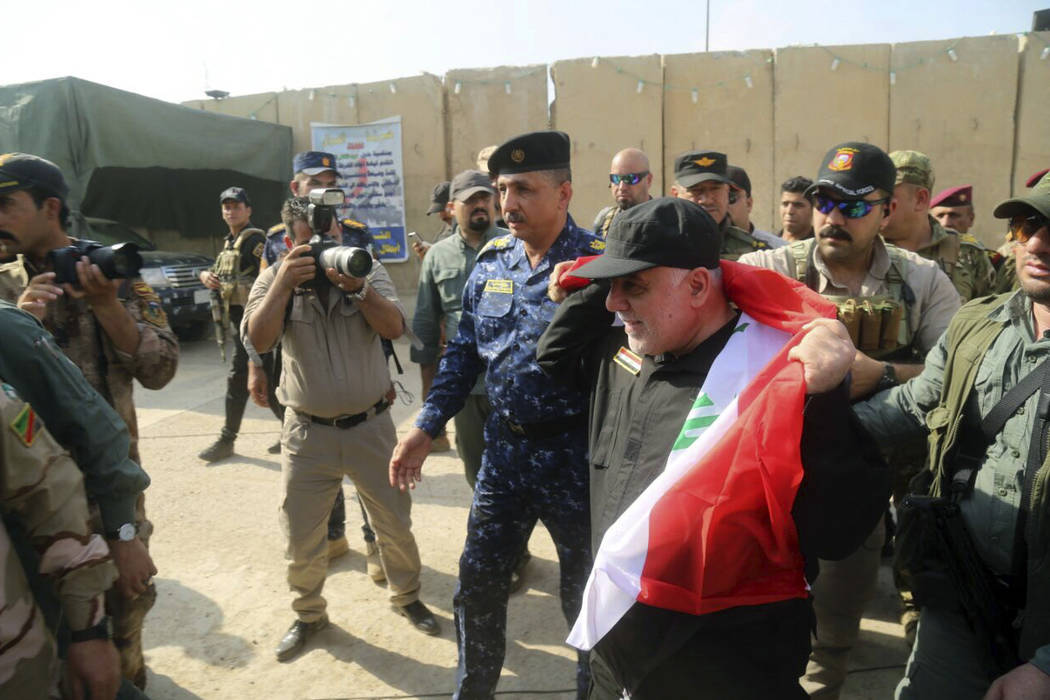 Iraq's Prime Minister Haider al-Abadi, center, holds a national flag upon his arrival to Mosul, Iraq, Sunday, July 9, 2017. Backed by the U.S.-led coalition, Iraq launched the operation to retake  ...
