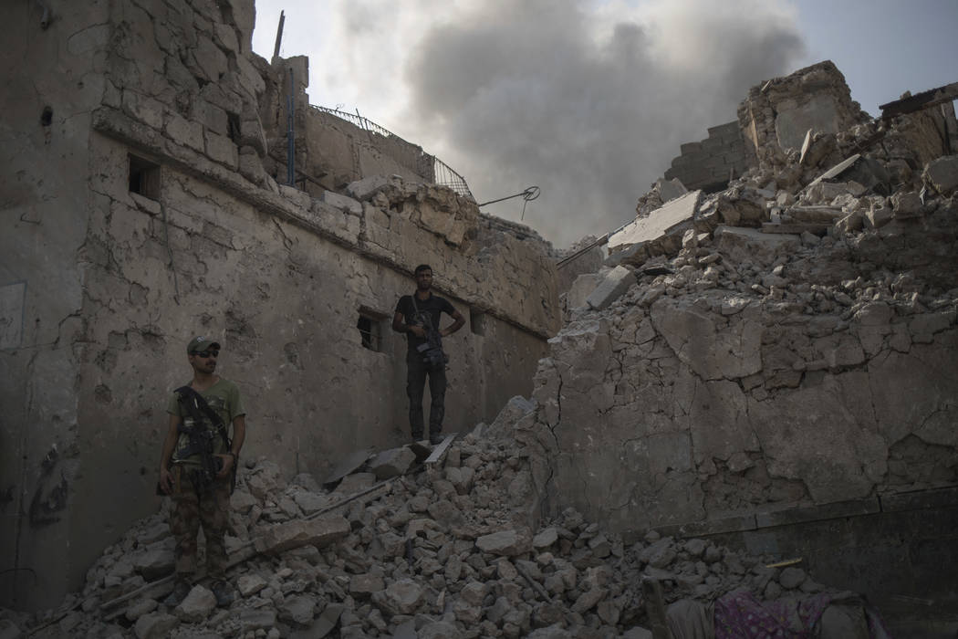 Iraqi Special Forces soldiers stand on the rubble of a damaged building as their fight against Islamic State militants continues in parts of the Old City of Mosul, Iraq, Sunday, July 9, 2017. (Fel ...