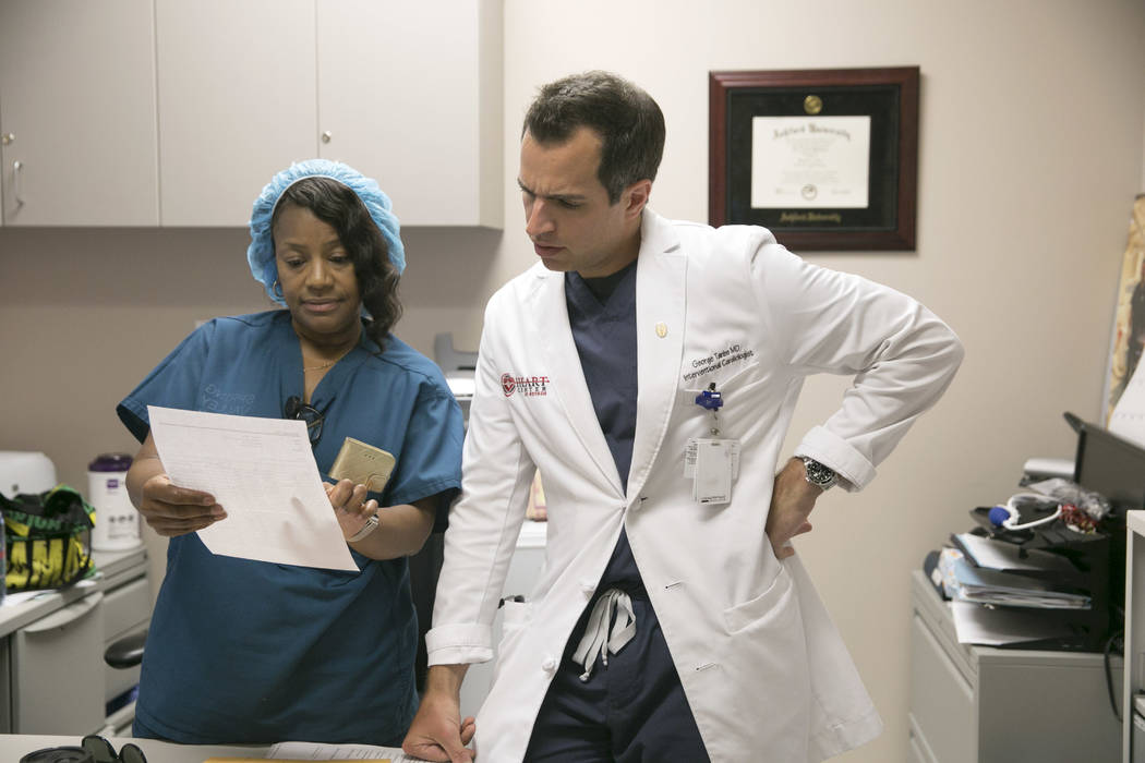 """Tina Williamson, left, clinical supervisor of the Catheterization Laboratory """"Cath Lab"""", and Dr. Georges Tanbe, right, an Interventional Cardiologist, look over patient paperwork in the """"Cath Lab"""" ..."""