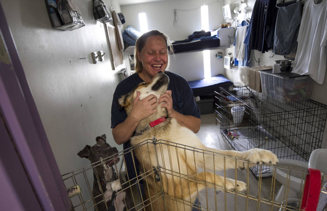 Inmate Erika Valenzuela stands inside her cell room with her dogs Kino, center, and Nalla inside the Pups on Parole cell block at the Florence McClure Women's Correctional Center in Las Vegas on T ...