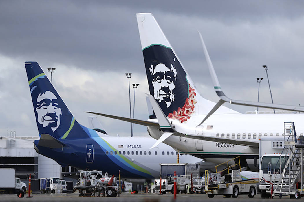 In this Monday, April 4, 2016, file photo, Alaska Airlines planes with the company's new livery and tail logo, left, and the old livery used to promote service to Hawaii, right, are shown parked a ...