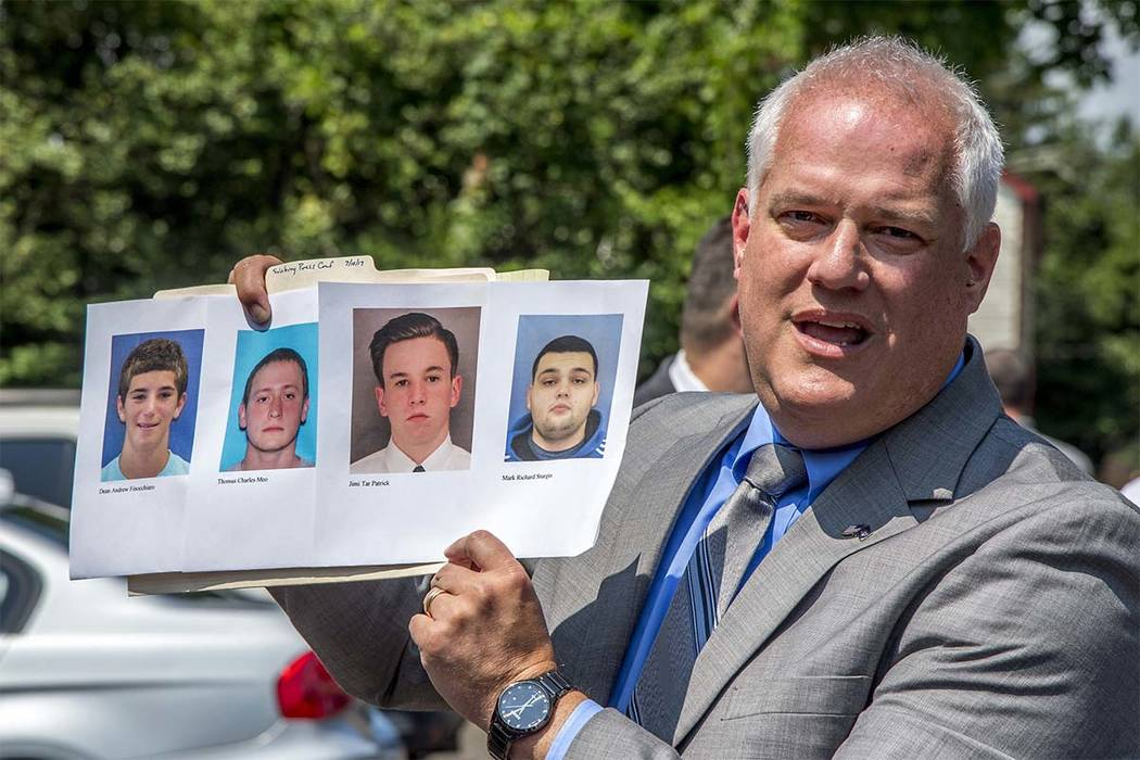 Bucks County District Attorney Matthew Weintraub holds up photos of four men who are missing during a news conference in Solebury Township, Pa., Monday, July 10, 2017. The four men, who went missi ...