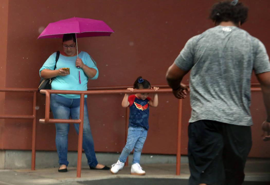 Pedestrians take shelter at Main Street hotel-casino during a quick rain shower on Tuesday, July 11, 2017, in Las Vegas. (Bizuayehu Tesfaye/Las Vegas Review-Journal) @bizutesfaye