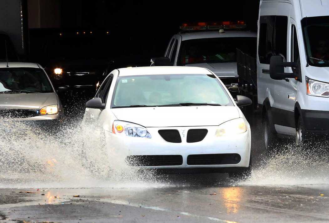 Motorists navigate through a flooded street on Bonanza Road during a quick rain shower on Tuesday, July 11, 2017, in Las Vegas. (Bizuayehu Tesfaye/Las Vegas Review-Journal) @bizutesfaye
