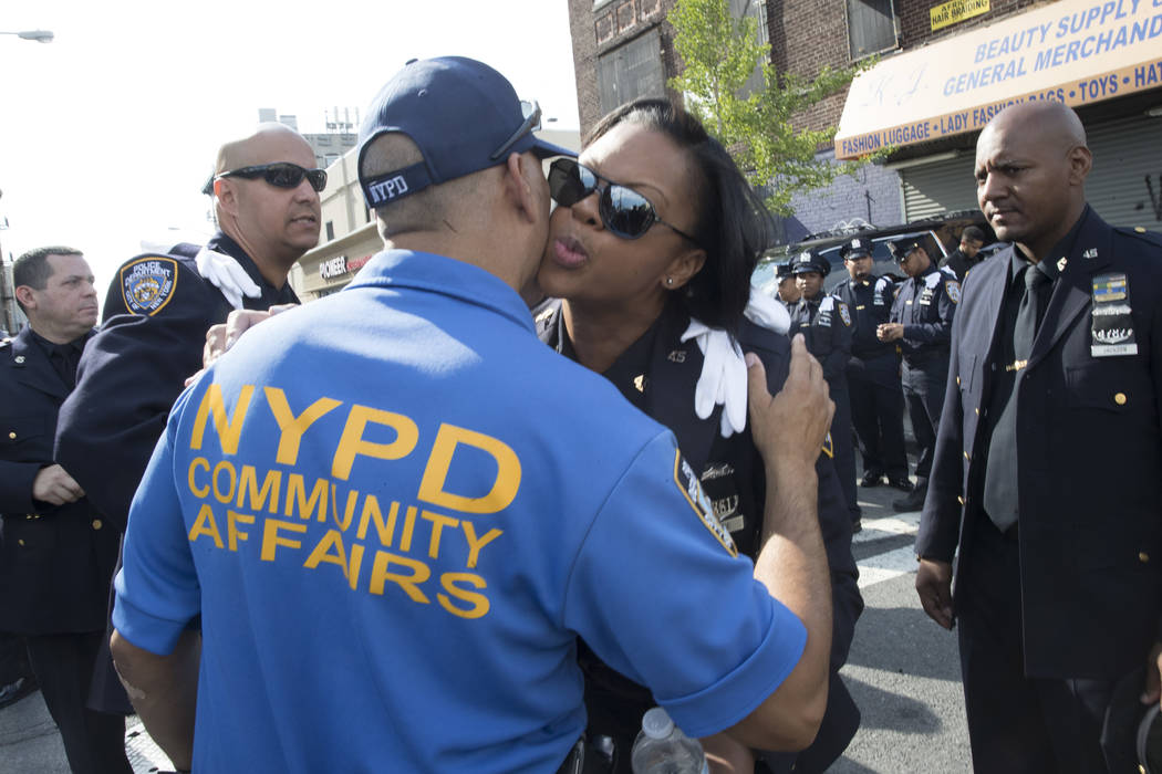 Police officer Nicy Chase hugs Detective June Caldero outside the World Changers Church in the Bronx borough of New York before the funeral service for slain New York police officer Miosotis Famil ...